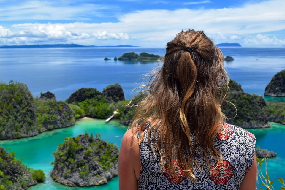 Girl looking out over Piaynemo, Raja Ampat, Indonesia