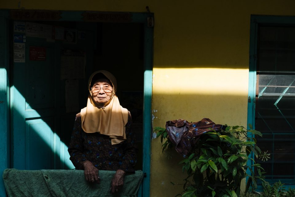 Old lady looks out from her house, Yogyakarta, Indonesia