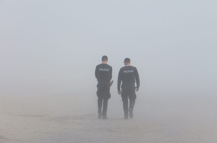 Two policemen walking away from the camera