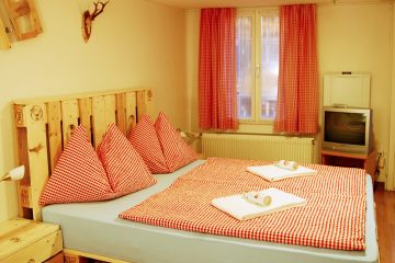 Red and white bedding in hotel toom