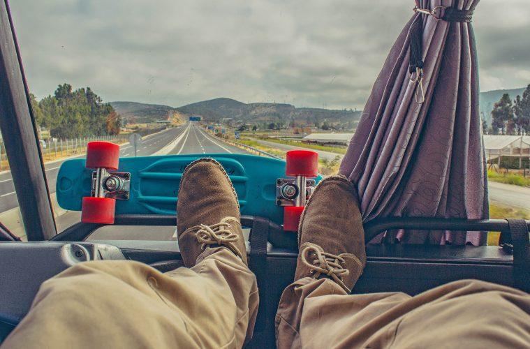 A man's feet up on the dashboard