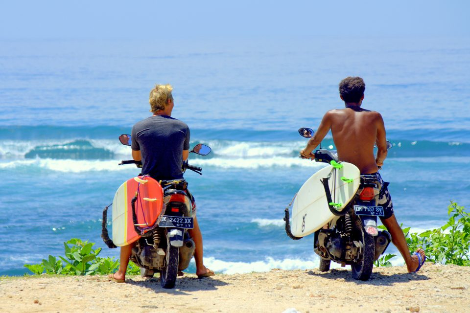 Two men on motorbikes with their surfboards