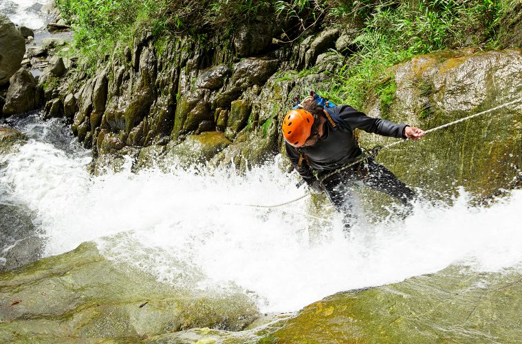 A woman abseiling down a waterfall