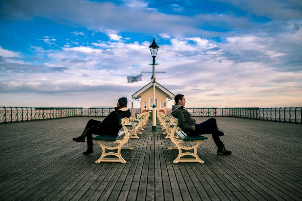 A couple sitting back to back on a pier