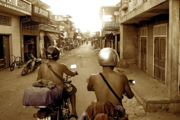 Two men riding motorbikes down a busy side street