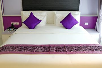 Double bed with two purple cushions