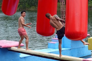 Two men on a balance beam over water