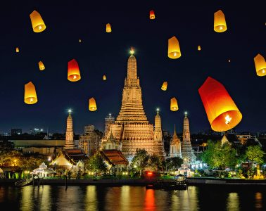 Multiple lanterns floating in the sky around a temple