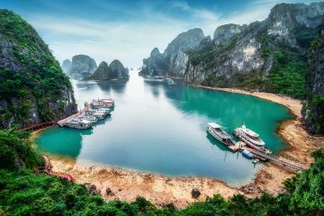 Boats moored in blue waters surrounded by rocky islands