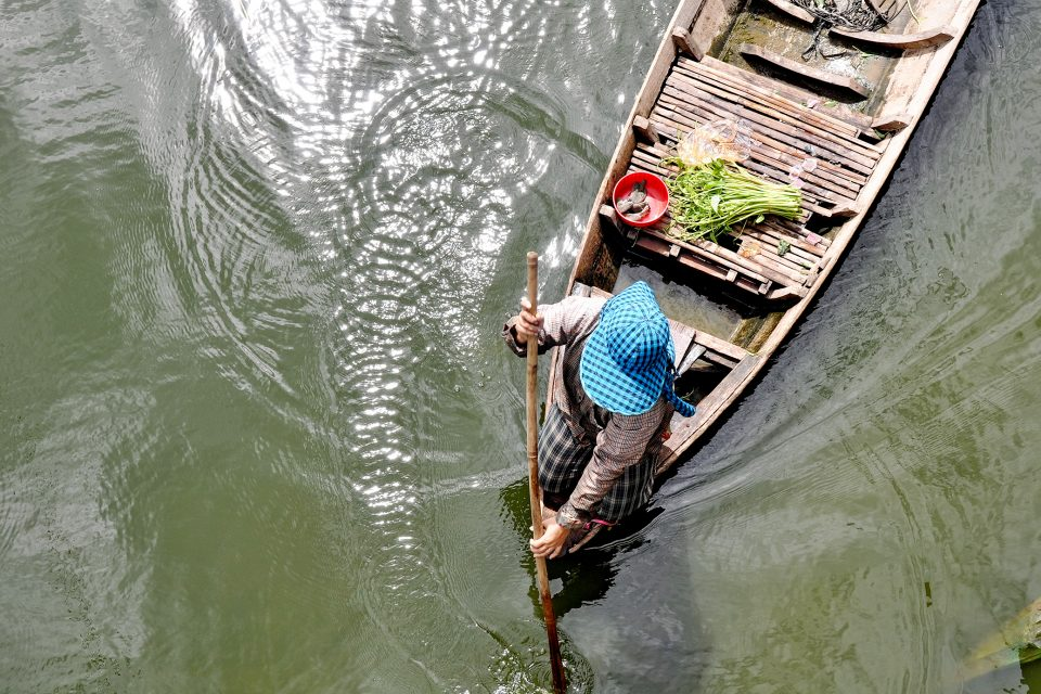 Ariel view of a woman punting a canoe