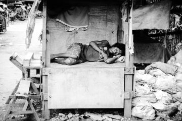 A woman sleeping in a wooden hut