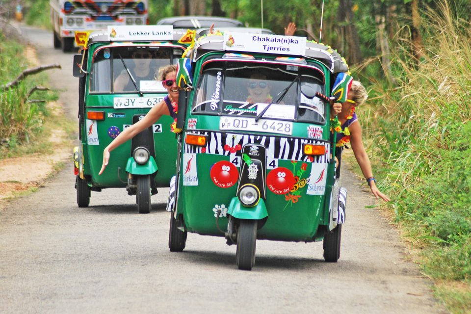 Two girls hang out of a tuk tuk on the Lanka Challenge