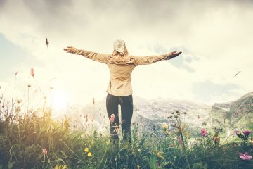 A person in a field with their arms outstretched