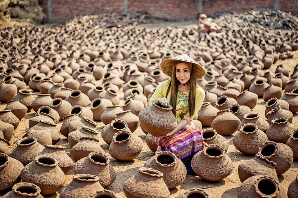 A woman surrounded by clay pots